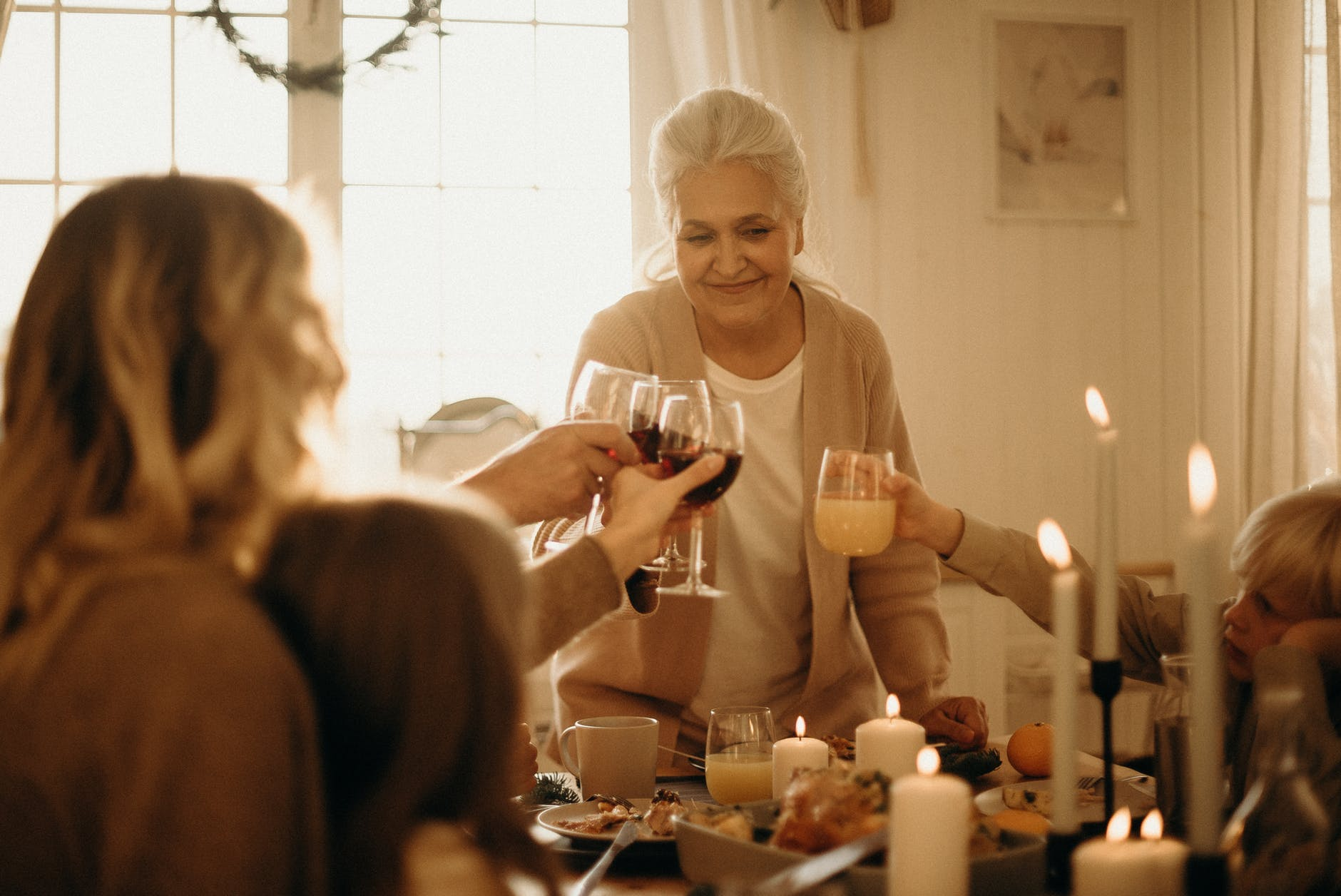 woman on gray cardigan standing near table doing cheers